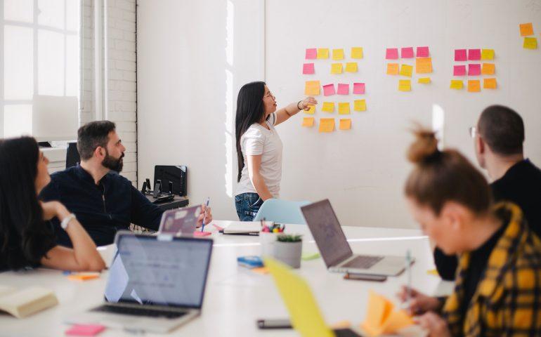 key. Steering Team Meeting Laptops auf Tisch fünf Leute im Hintergrund eine Post it Wand